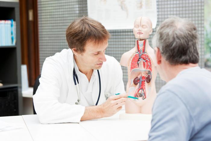 [Arzt zeigt einem Patienten die Blase an]