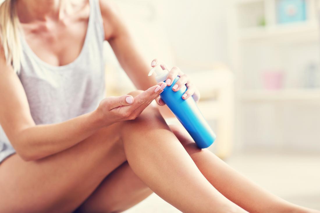 Mulher aplicar protetor solar na pele.