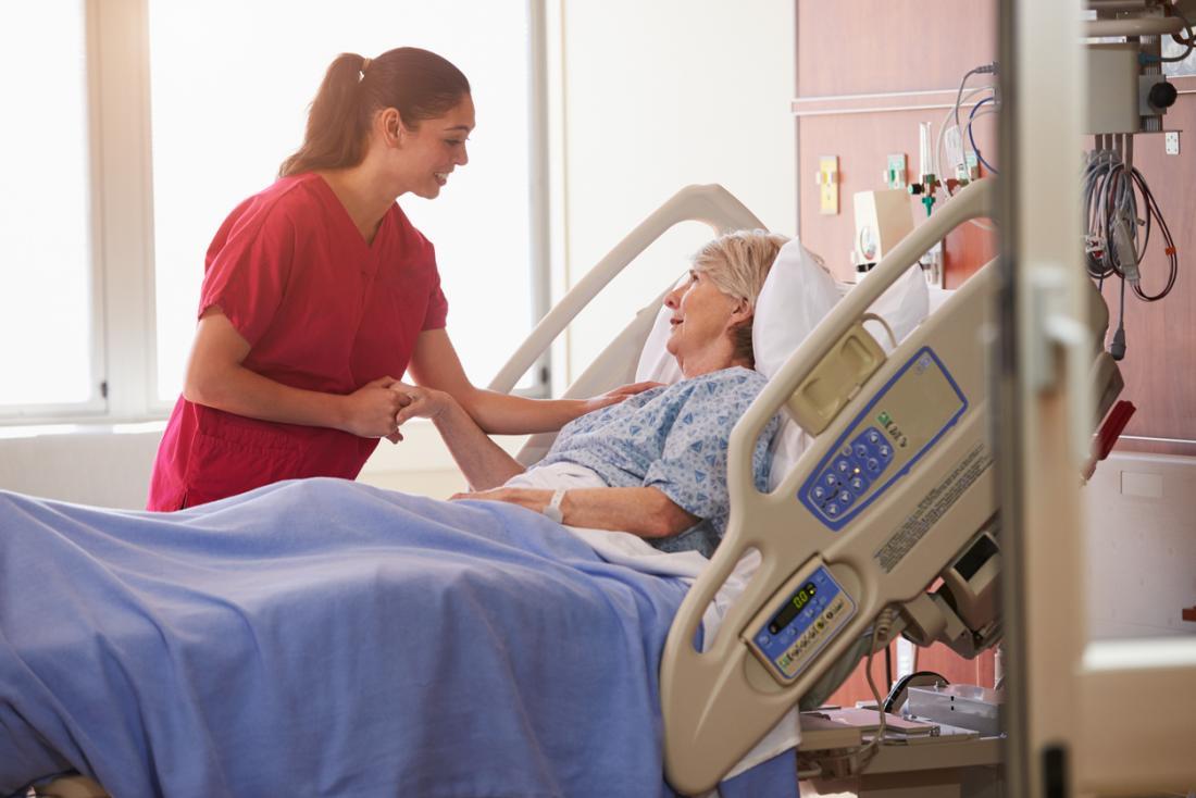 Älterer weiblicher Patient im Krankenhausbett mit Krankenschwester.