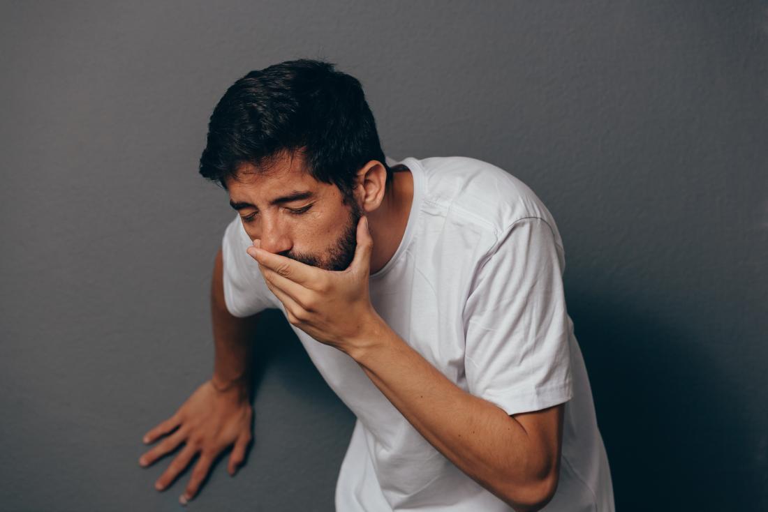 Homme sur le point de vomir de la bile verte ou jaune couvrant sa bouche avec sa main.