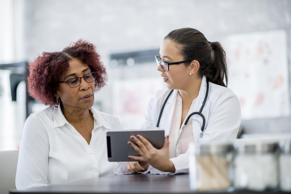 Une femme âgée parle au médecin qui lui montre des informations sur l'écran de la tablette.