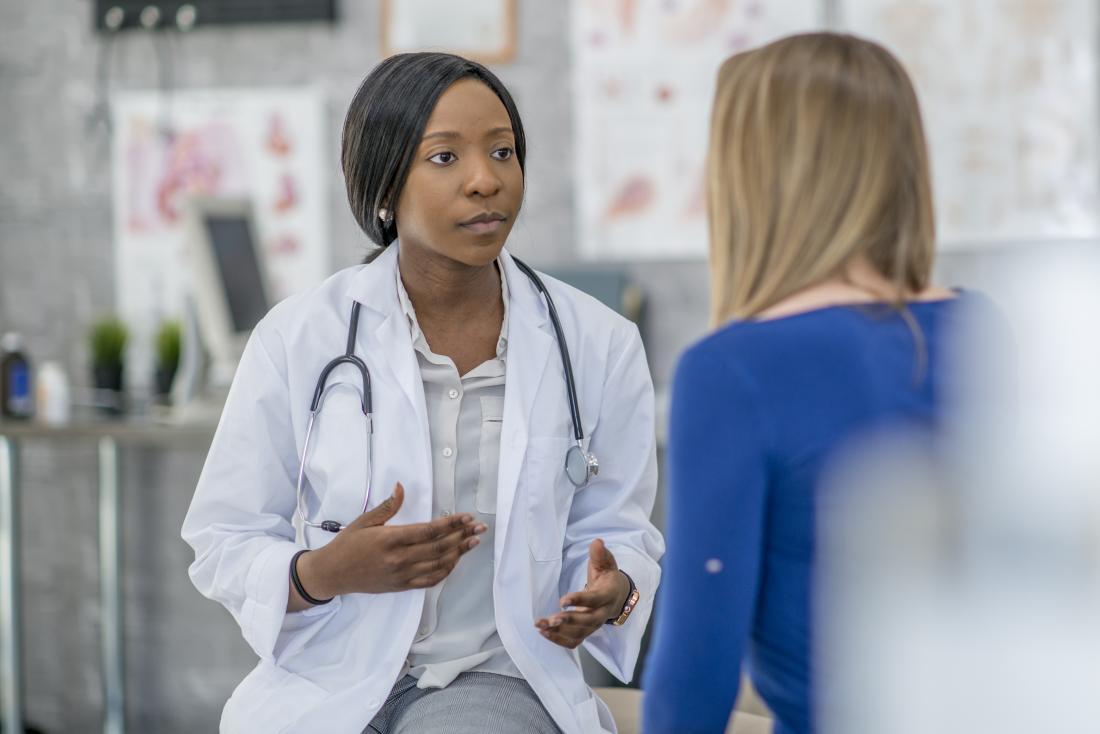 Kobiety doktorski inmiddle wyjaśniać coś żeński pacjent w jej biurze.