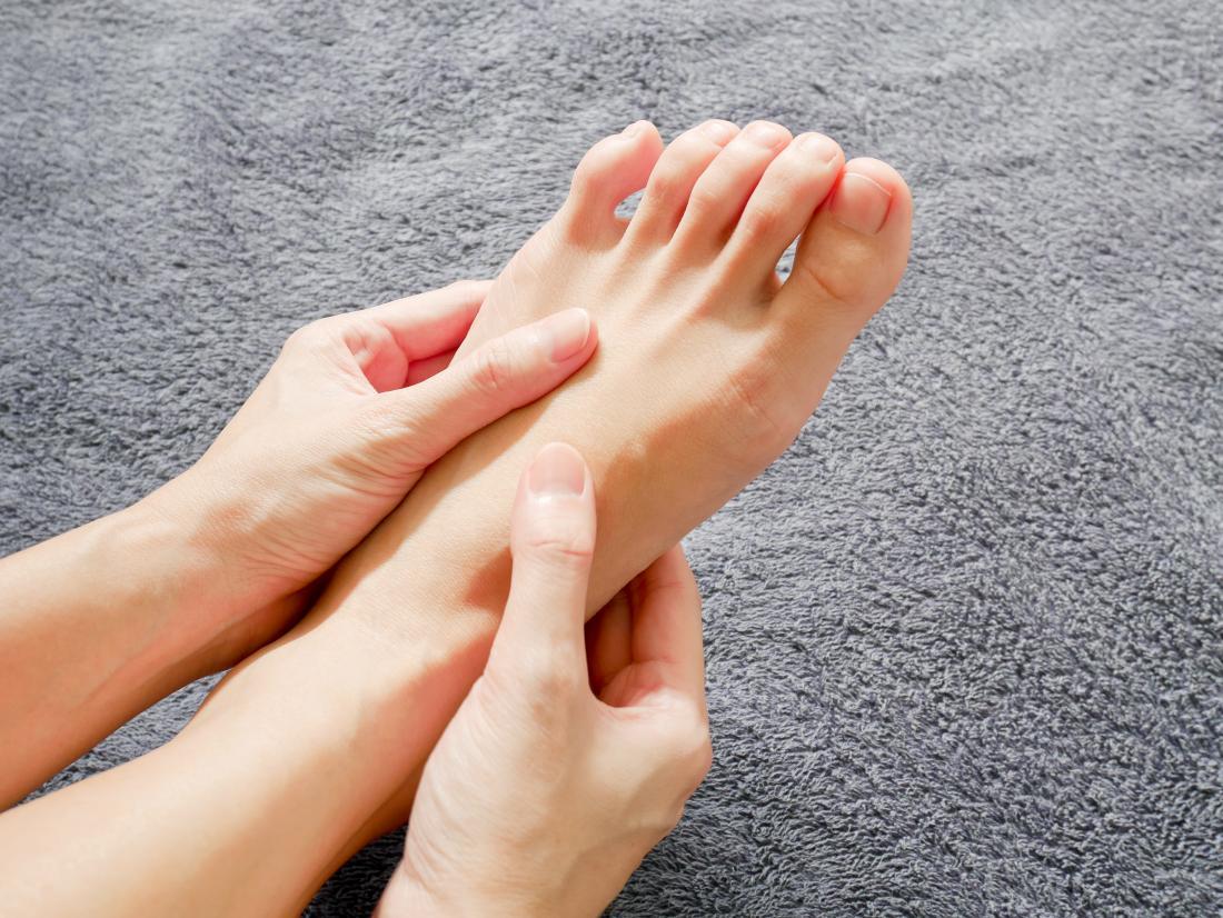 足と足のしびれのために彼女の足を持っている女性