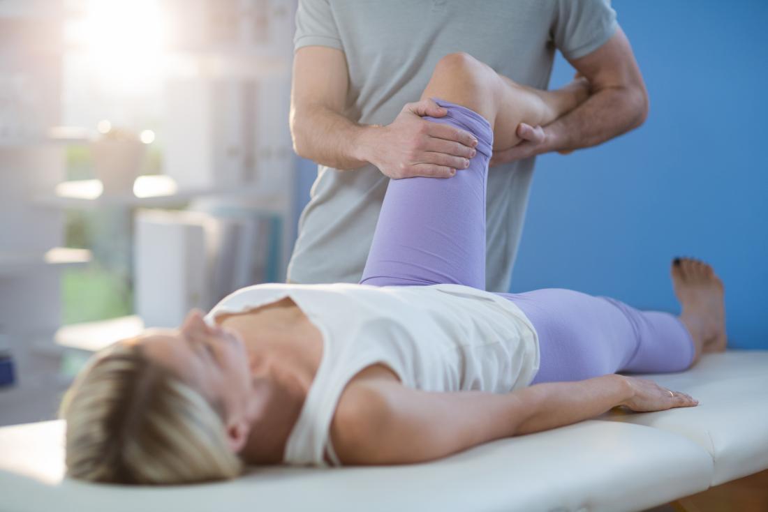 足と足のしびれのために足のマッサージをしている女性