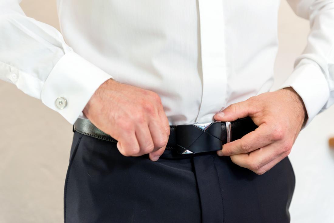 Mann mit weißen Beulen auf seinem Penis, der seinen Gurt oben bindet.