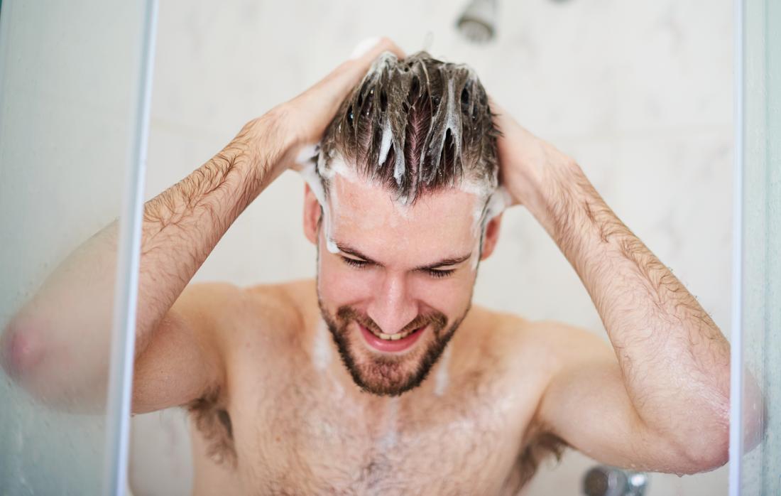 Man wäscht sich und Haare mit Shampoo in der Dusche unter Beibehaltung der guten Hygiene.