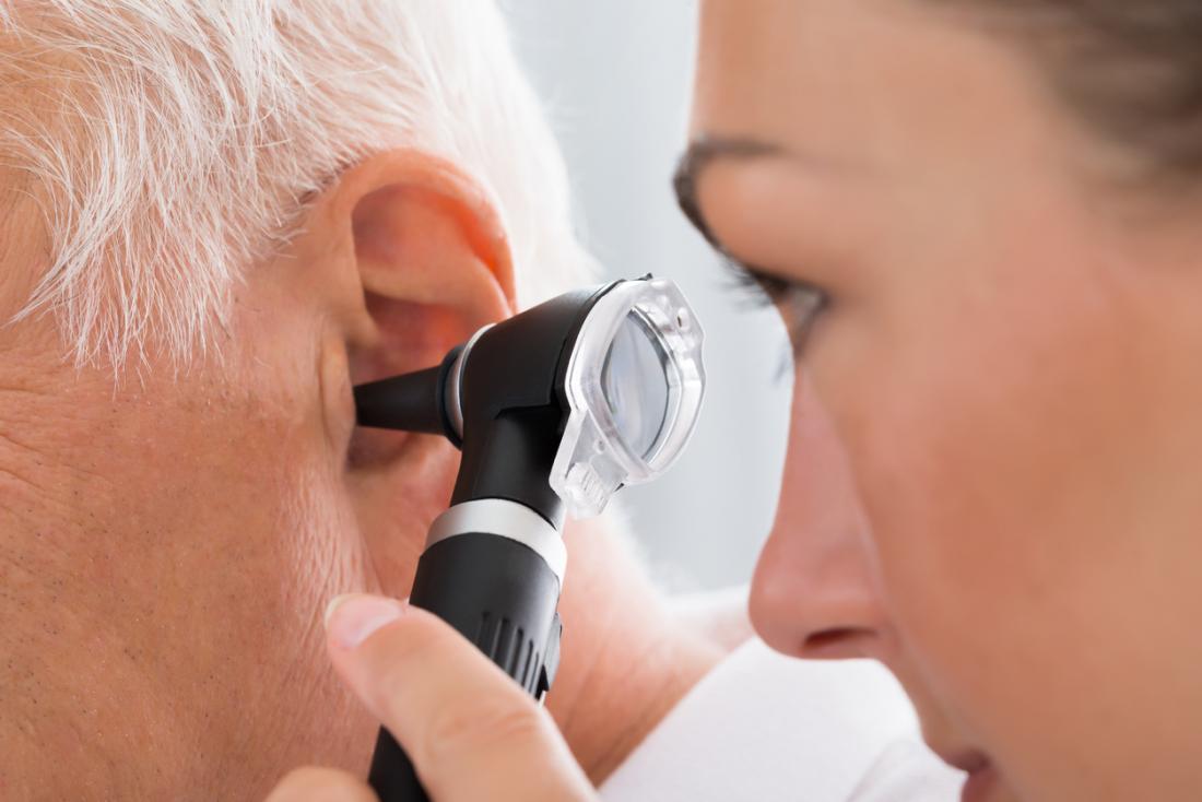 Doktor, der ein älteres bemannt, verfolgt Ohr