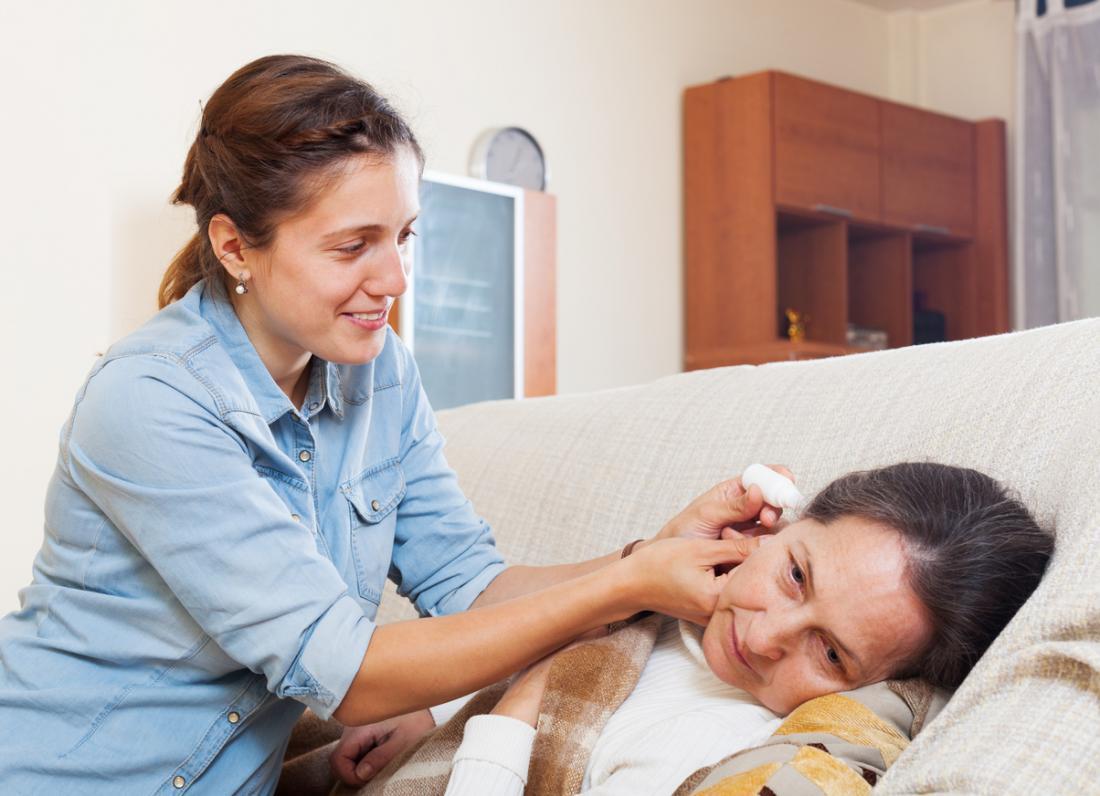 Ohrentropfen werden von einer Tochter an ihrer Mutter verabreicht