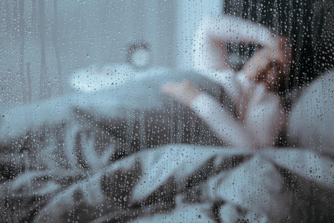 Senhora na cama olhando pela janela perguntando por que ela sempre se sente doente