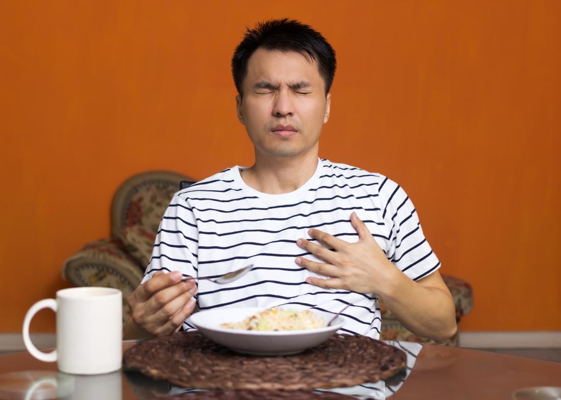 Човекът яде храна, страдаща от киселинен рефлукс, докосвайки гърдите в болка.