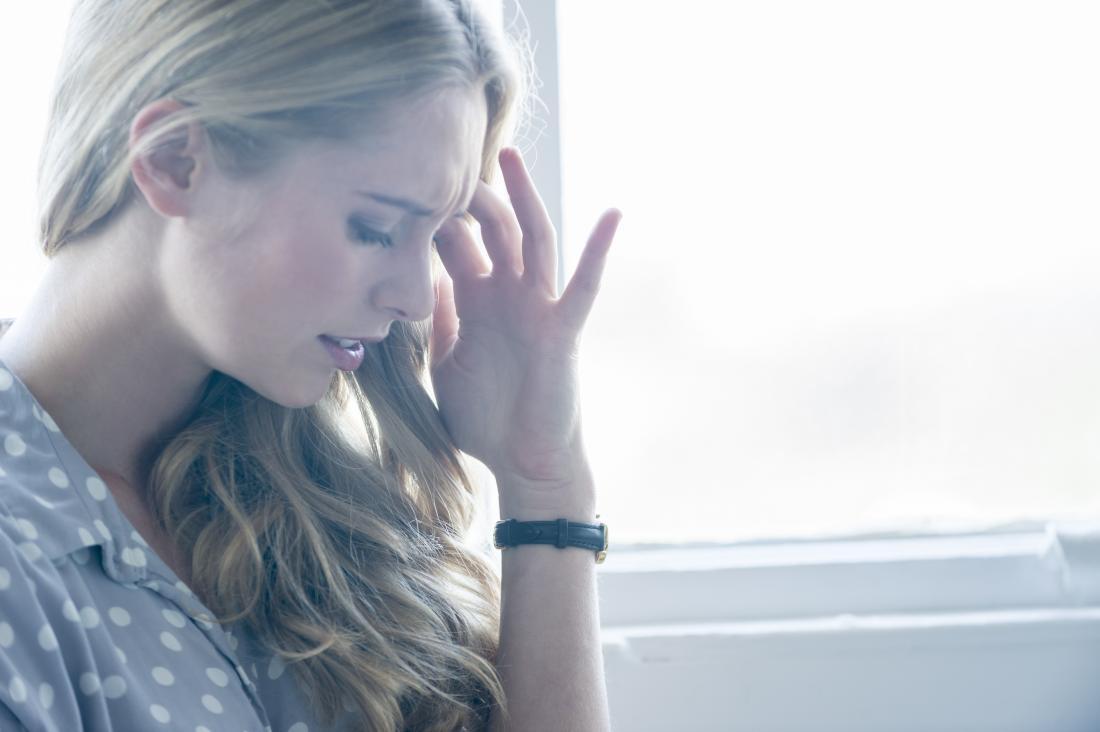 жена, която държи главата си в лека болка, вероятно има замайване и умора