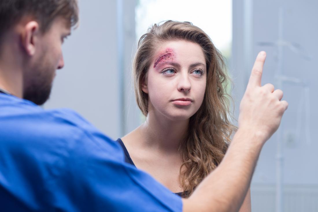 Frau mit Kopfverletzung bei den Ärzten mit möglichen Gehirnerschütterung, die Schwindel und Müdigkeit verursacht