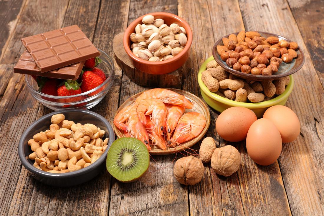 Allergiker auf Holztisch, darunter Cashewnüsse, Pekannüsse, Haselnüsse, Mandeln. Schokolade, Erdbeeren, Schalentiere, Walnüsse, Eier und Kiwi.