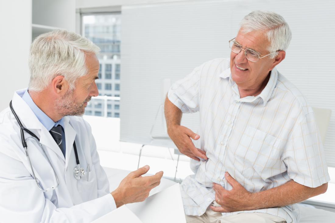 Älterer Mann an den Doktoren, die auf dem Bett zeigt auf Seite des Magens in den Schmerz sitzen.