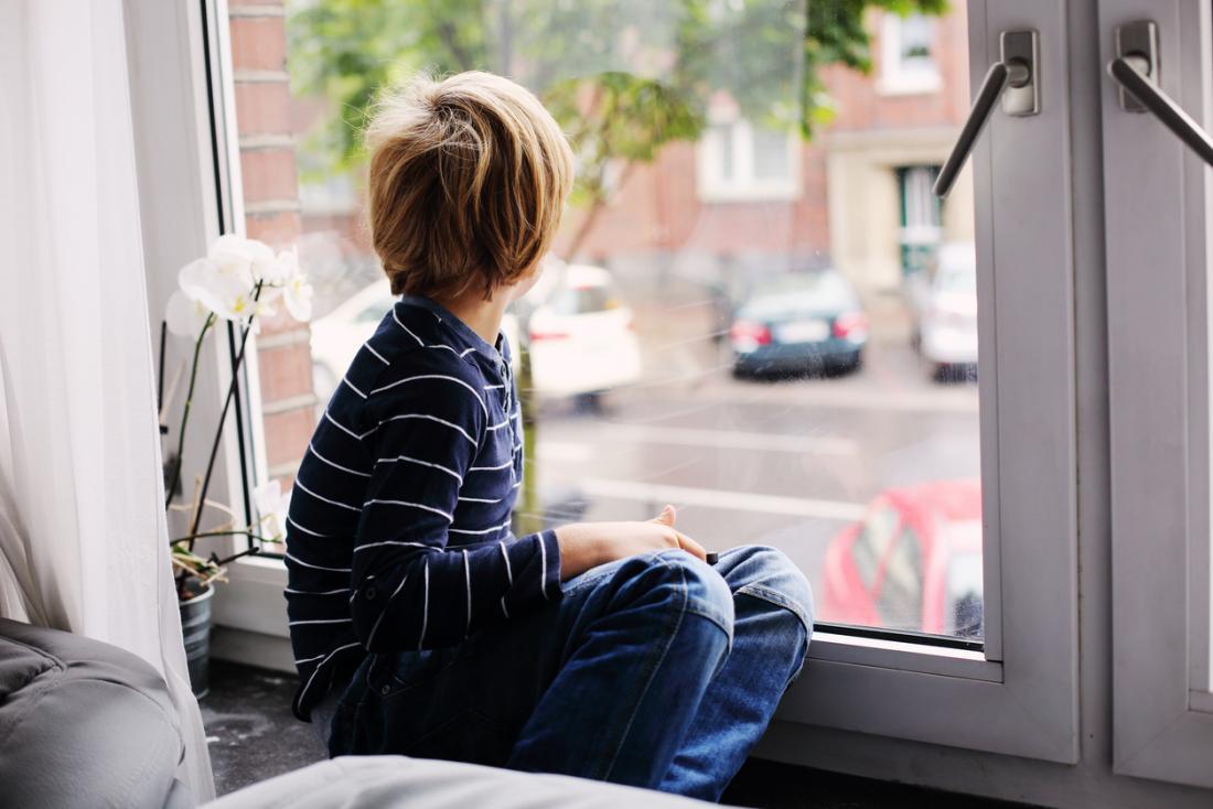 Rapaz, olhando pela janela.