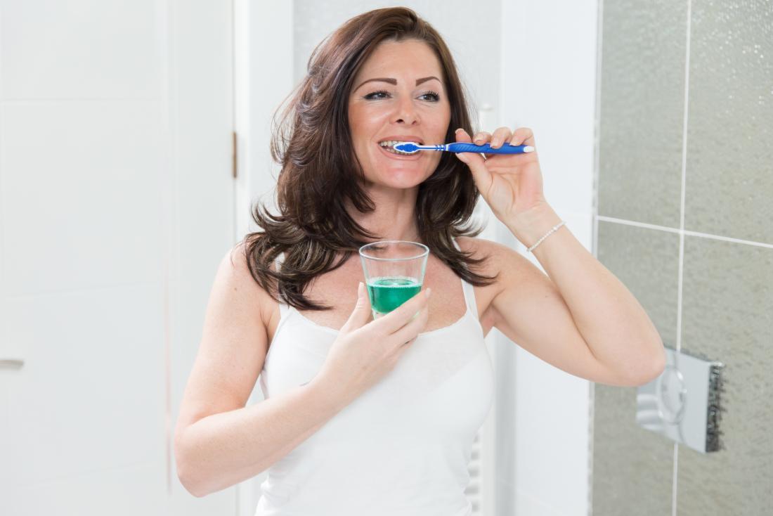 Frau, die ihre Zähne säubert und Glas Mundwasser hält