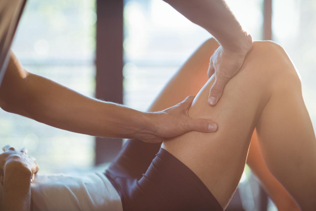 Person, die Sport-Physiotherapie-Massage an ihren Oberschenkeln erhält.