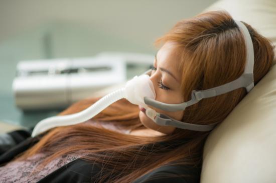 Femme avec l'apnée du sommeil en utilisant la machine de cpap