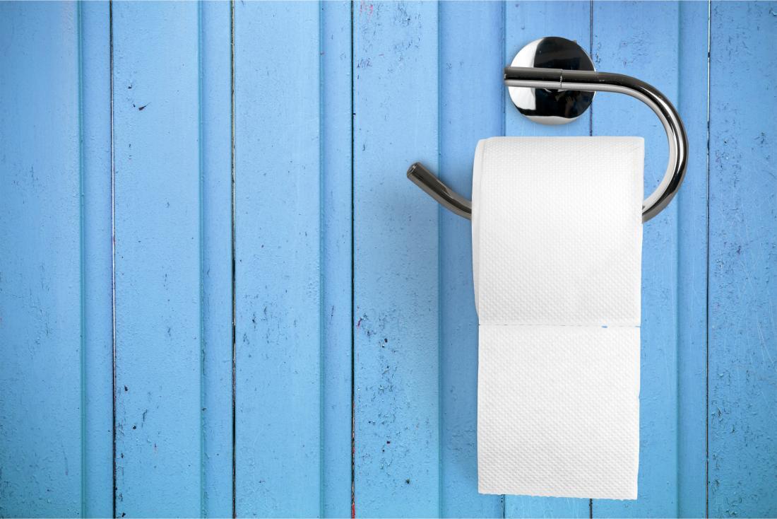 Toilettenpapier auf Halter auf der blauen Wand, die Blut beim Abwischen darstellt