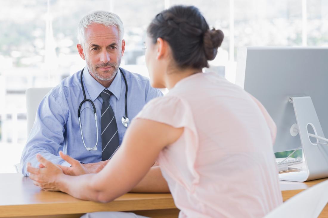 Weiblicher Patient, der mit männlichem Doktor in seinem Büro spricht.