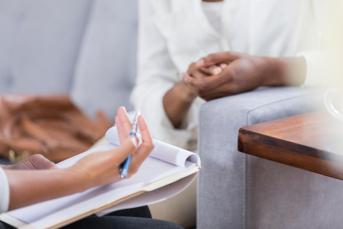 Consulente che tiene appunti che spiegano situazione al paziente.
