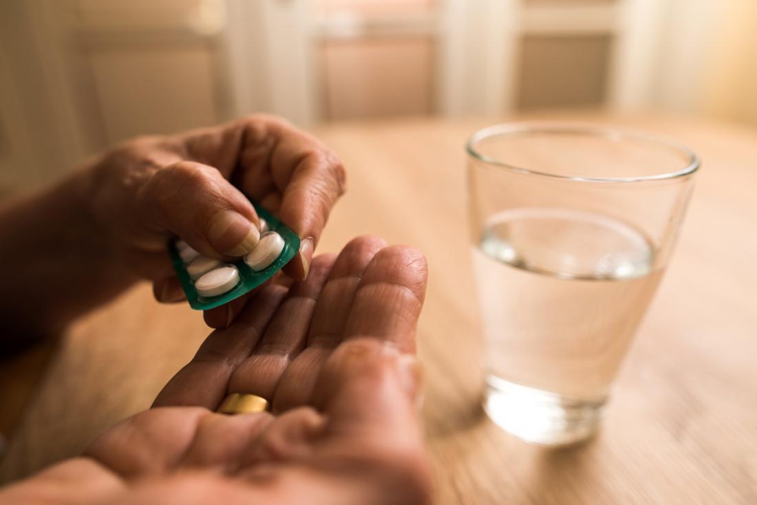 người cao tuổi uống thuốc giảm đau từ vỉ thuốc bằng một ly nước.