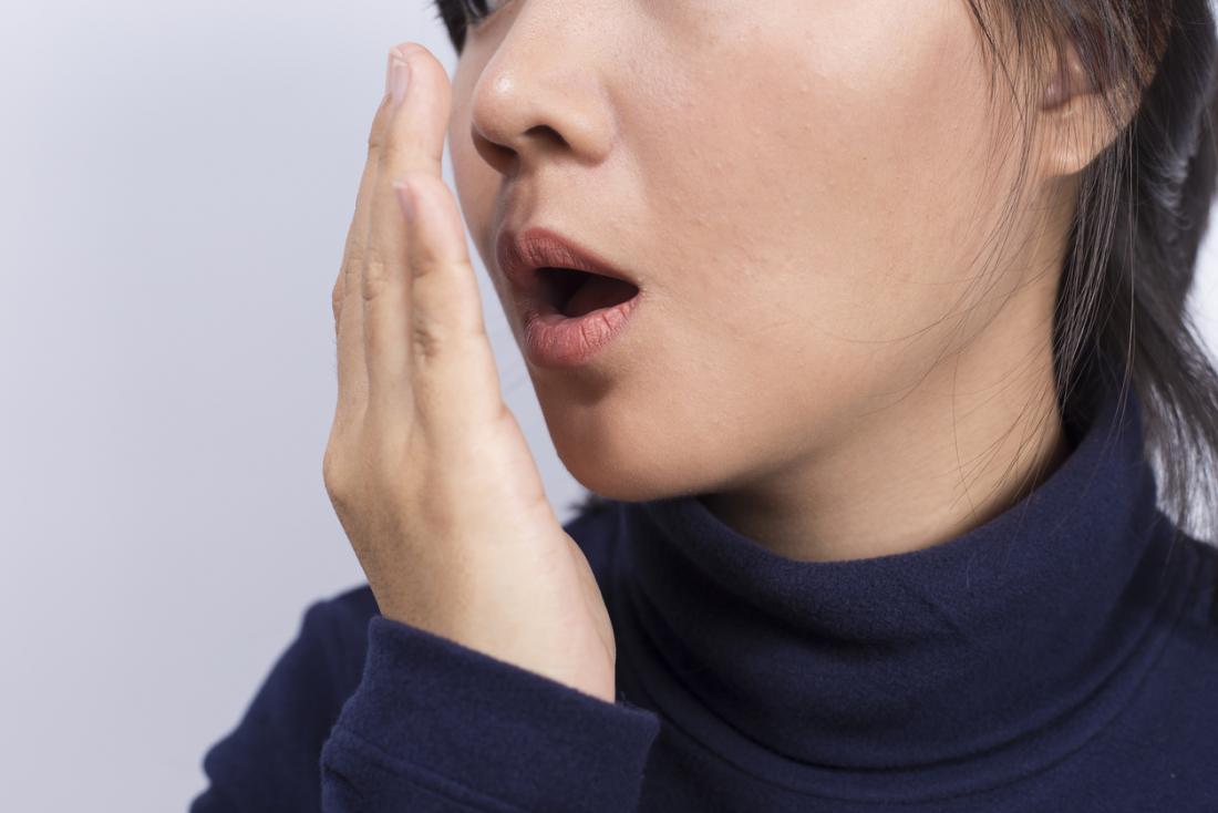 彼女の息が彼女の口の前で彼女の手を保持することによってどのように嗅ぐかチェックする女性。