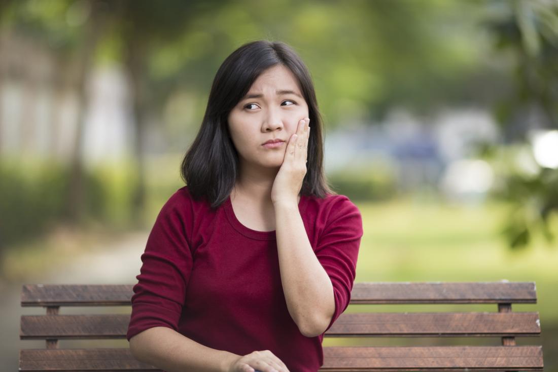 Người phụ nữ ngồi trên ghế đá công viên ôm má đau vì đau răng hoặc đau lưỡi.