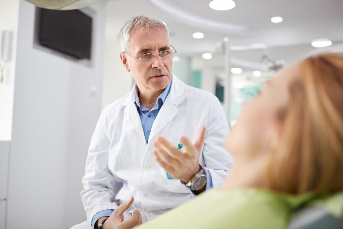 Bác sĩ phẫu thuật nha khoa nói chuyện với bệnh nhân.