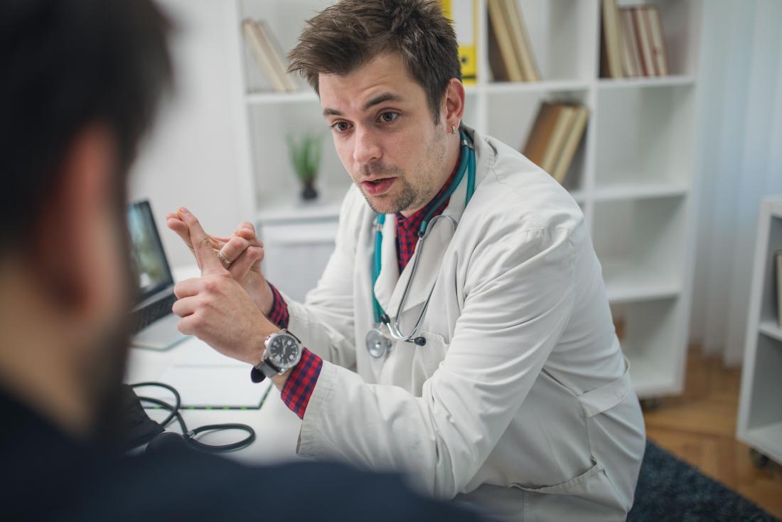 Medico maschio che elenca le cause della condizione per rendere paziente