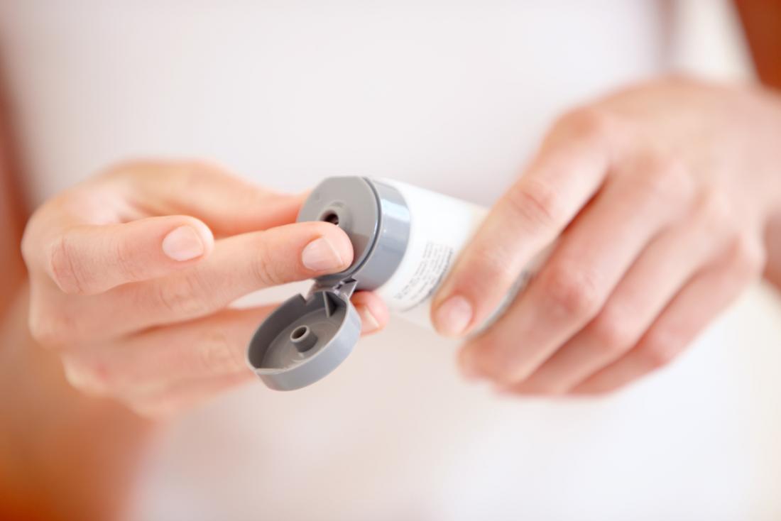Femme pressant une crème, une lotion ou une pommade d'un tube sur le bout de son doigt.