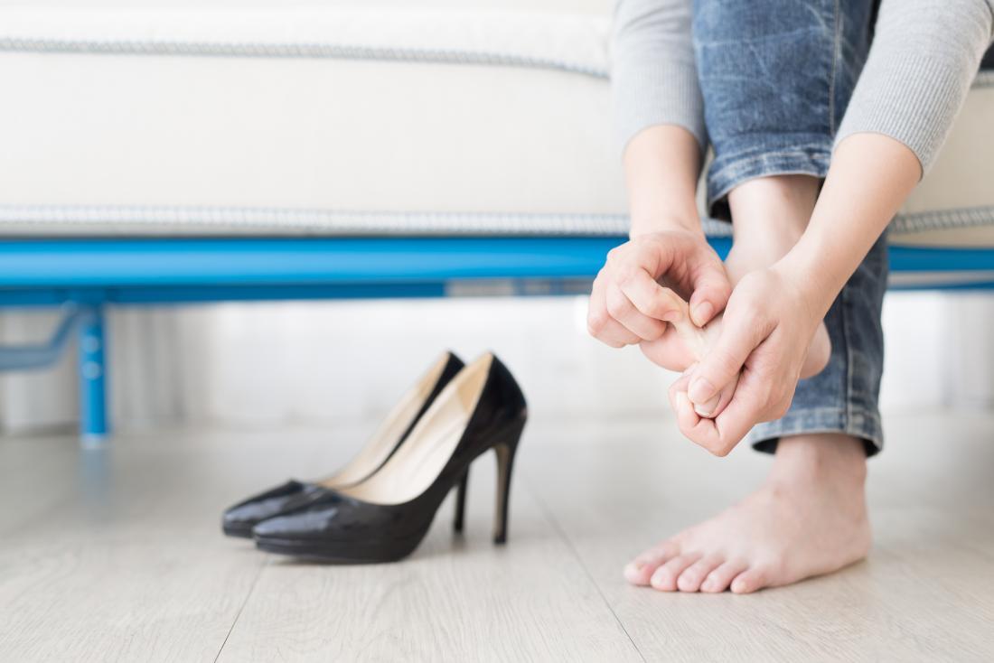 A mulher tirou os sapatos de salto alto e está inspecionando os pés e os pés descalços.