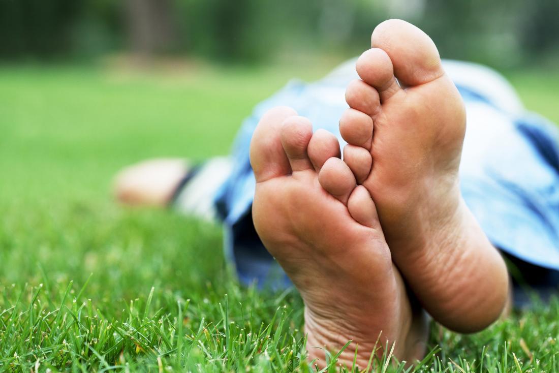 Pés descalços da pessoa que encontra-se na grama.