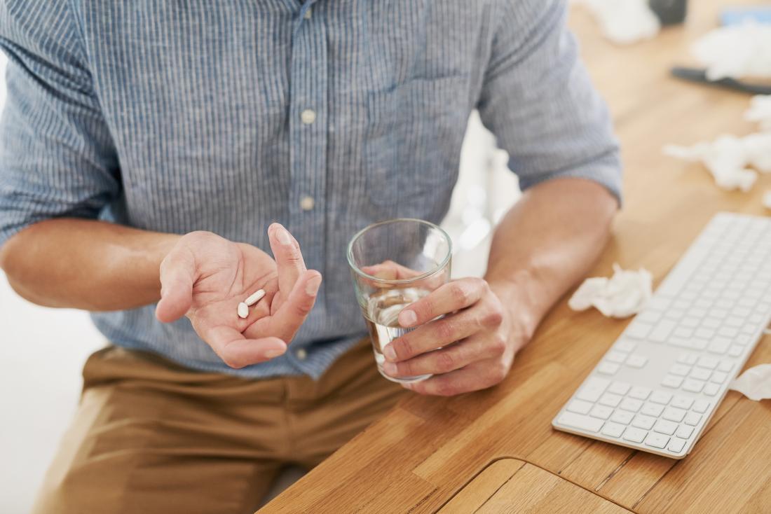 職場で補給ビタミンを摂取している男性。