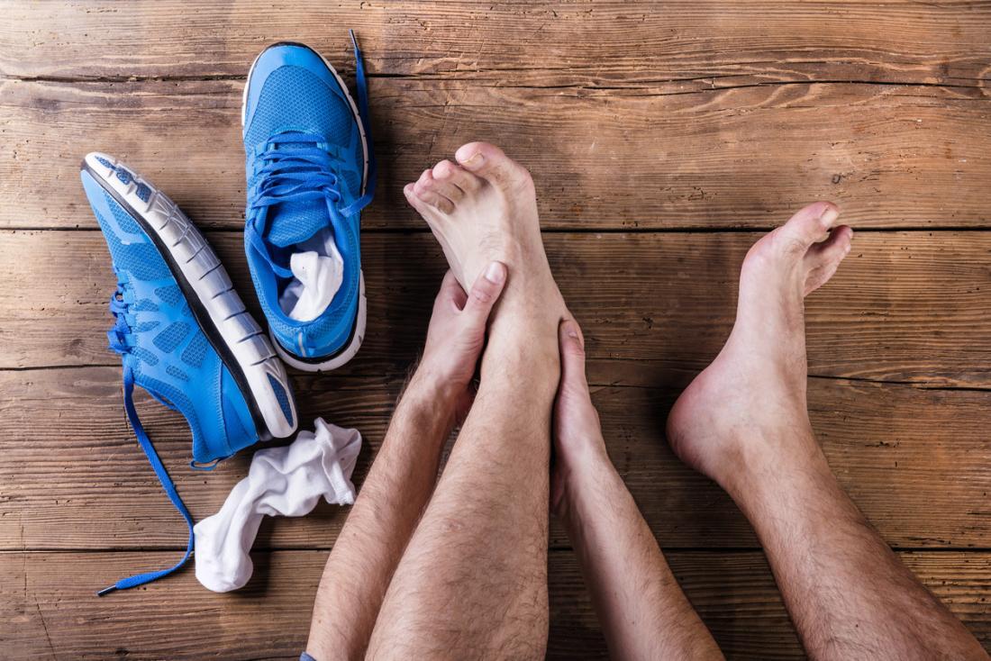 Verletzter Läufer, der seinen Knöchel und seine Oberseite seines Fußes hält.