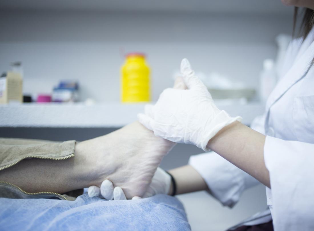 Fußarzt, der Patientenfuß kontrolliert.