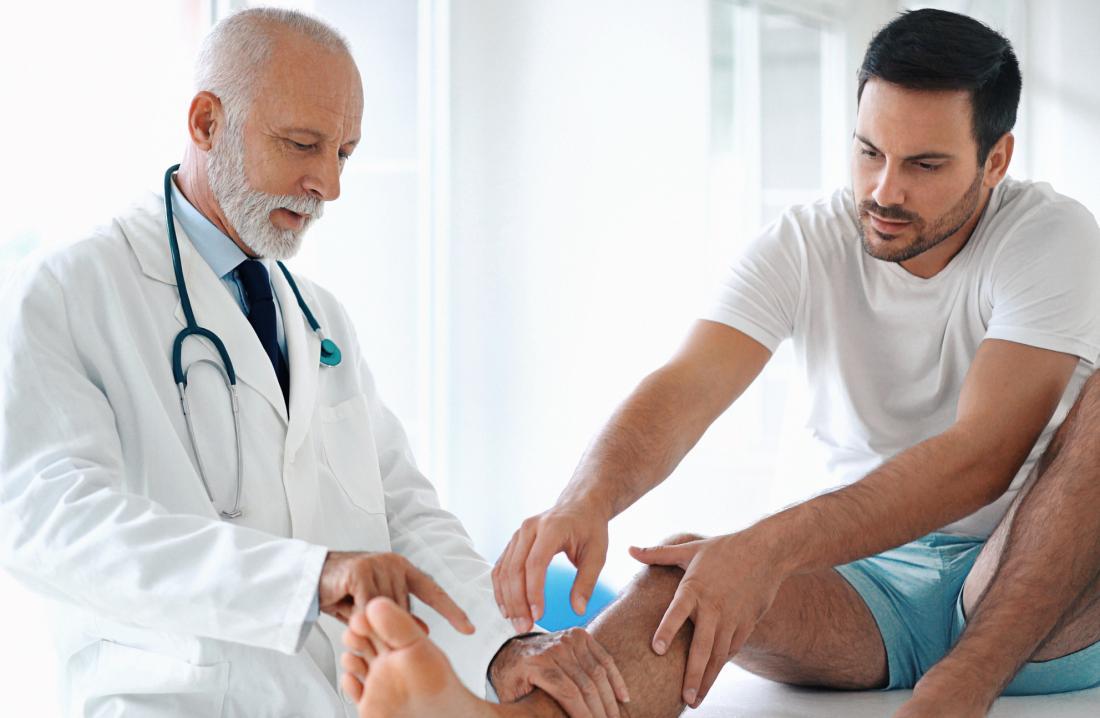 Dottore guardando la caviglia dell'uomo mentre si siede sul lettino.