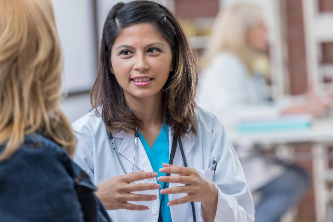 Bir hastayla konuşan doktor, elleriyle işaret ediyor.