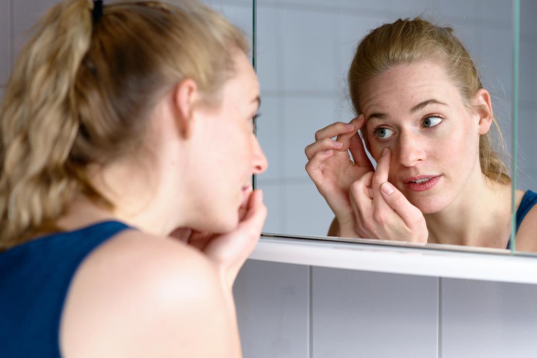 Mulher inspecionando cílios ingrown no espelho do banheiro