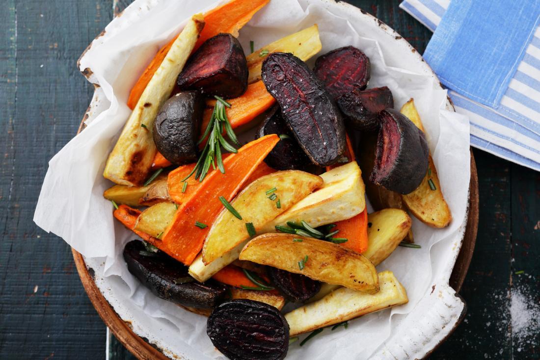 Légumes rôtis, y compris les pommes de terre, les carottes, les betteraves et les panais dans un bol.