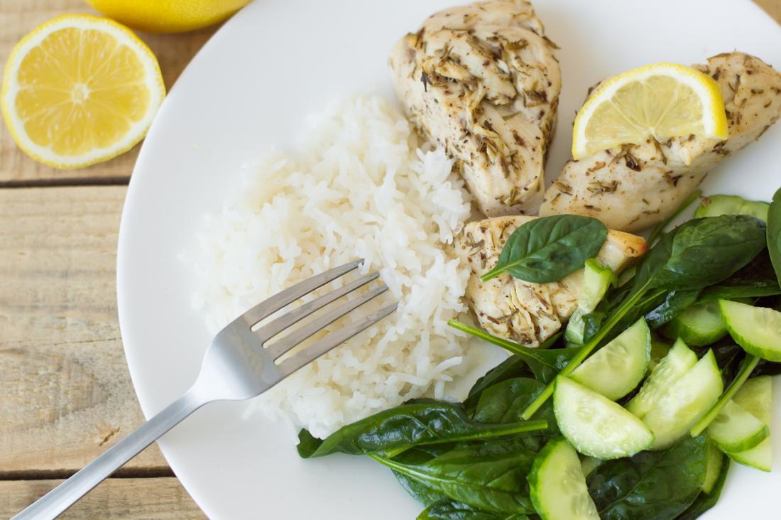 Une assiette de nourriture comprenant du riz blanc, du poulet, du citron et de la salade.