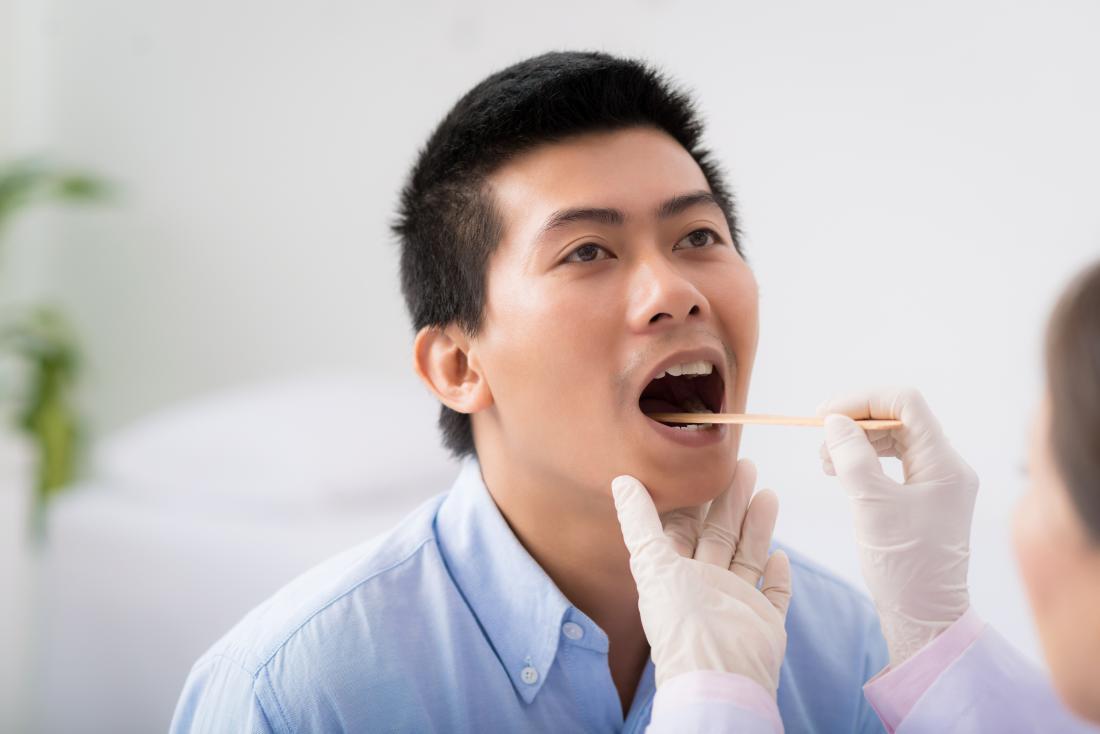 Човек, имащ кървене на езика и гърлото, инспектиран от лекар, използващ депресор на езика.