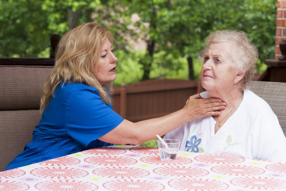 老人の喉を尋ね、卒中後に嚥下する看護師は、舌に影響を与えた。