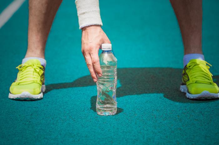 男は走っている道で水を拾うために屈む