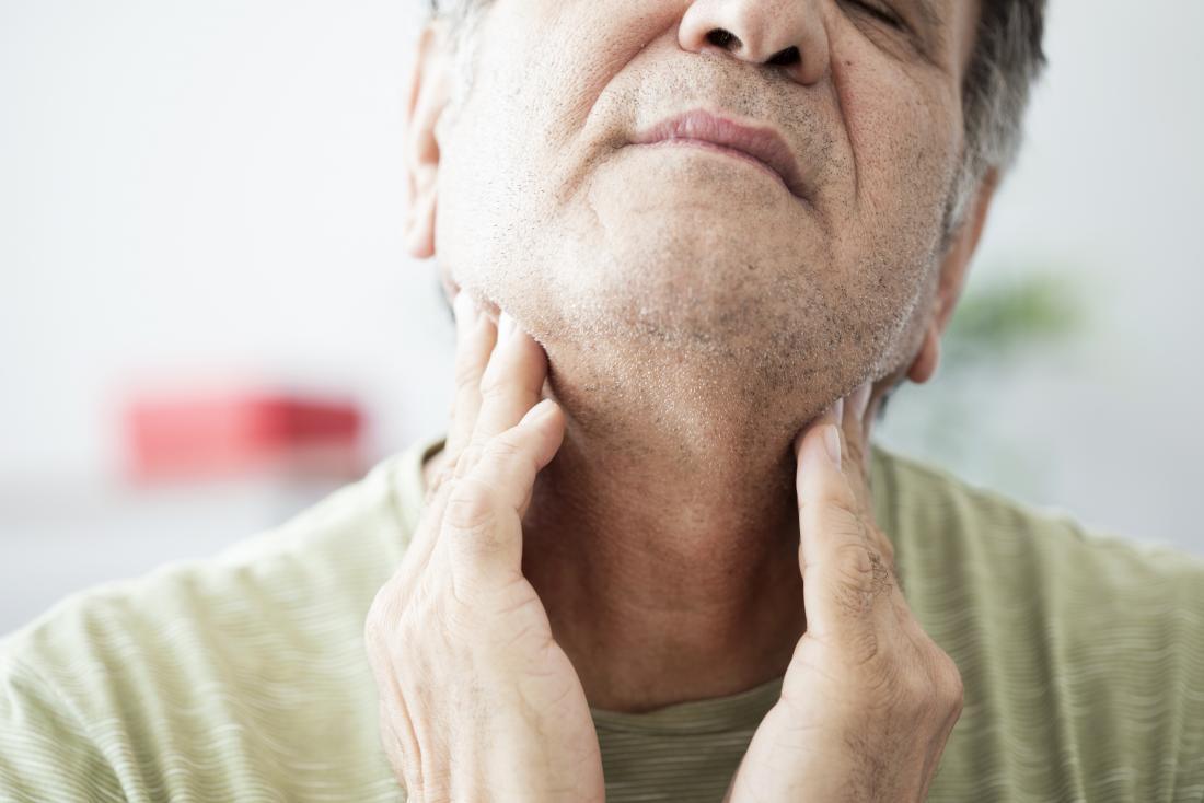 Maux de gorge d'un côté chez l'homme tenant les côtés du cou.
