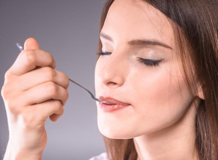 Eine Frau mit geschlossenen Augen isst etwas Essen von einem Metalllöffel