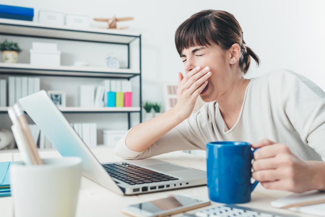 Femme au bureau avec bâillement de boisson chaude