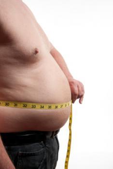 ウェストを測定する肥満男性