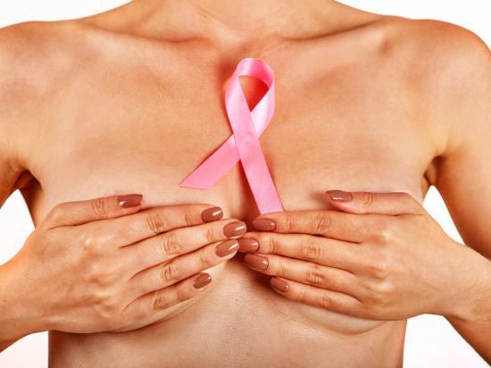 Pani trzyma piersi z różową wstążką na piersi