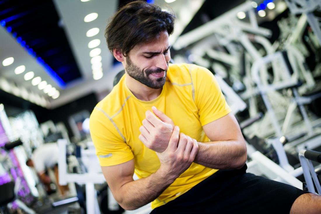 Mann, der sein verletztes Handgelenk nach Übung hält.